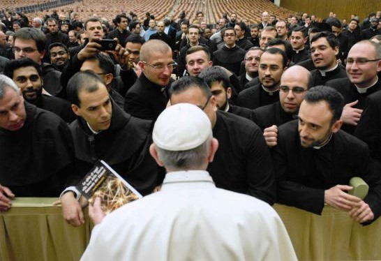 A priest presents the Pope with the book